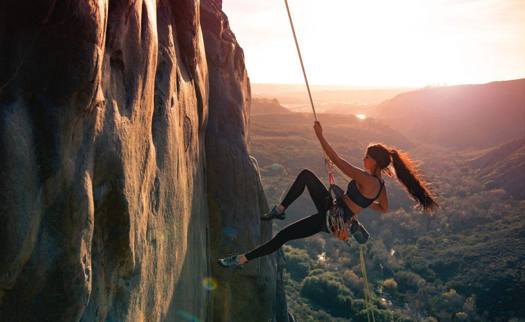 Woman rock climbing with a sunset behind